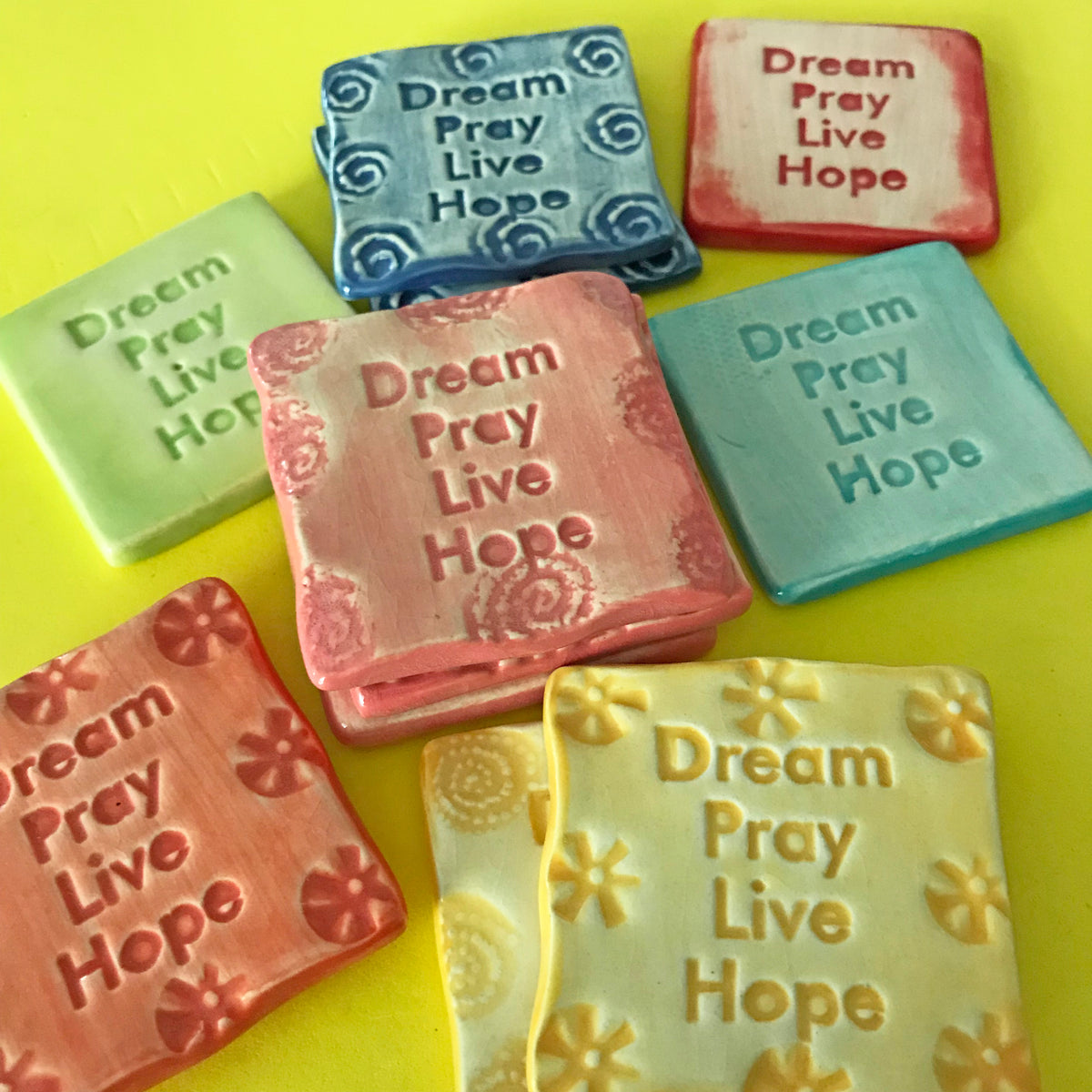 "A magnet offering a message of support: ""Dream, Pray, Live, Hope.""  Handmade ceramic."