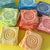 Spiral Sun motif pressed into soft clay to become our unique, colorful and affordable refrigerator magnets.