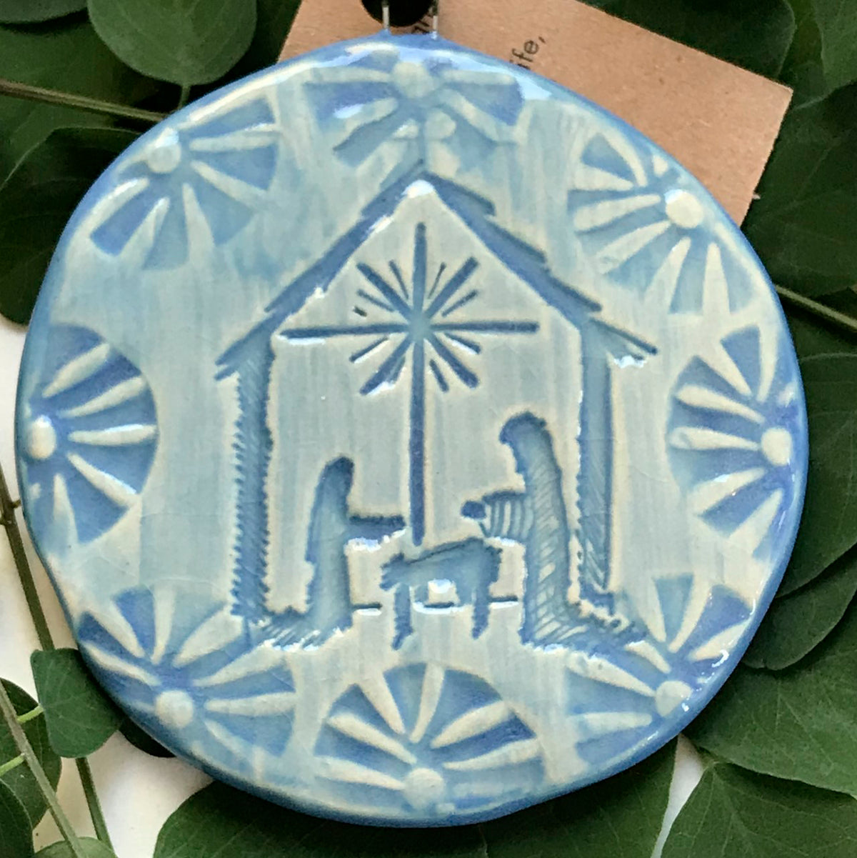 A traditional nativity scene handcrafted Christmas ornament glazed in a soft blue grey.