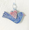 Handmade ornament shaped in folk art bird style, glazed with cobalt blue and heart wings.