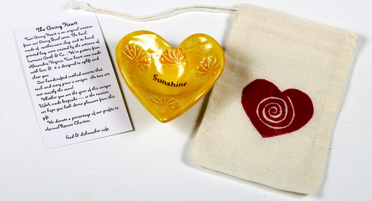 Lorraine Oerth Giving Heart with the word Sunshine glazed in a cheerful yellow color.  item is crafted by hand.