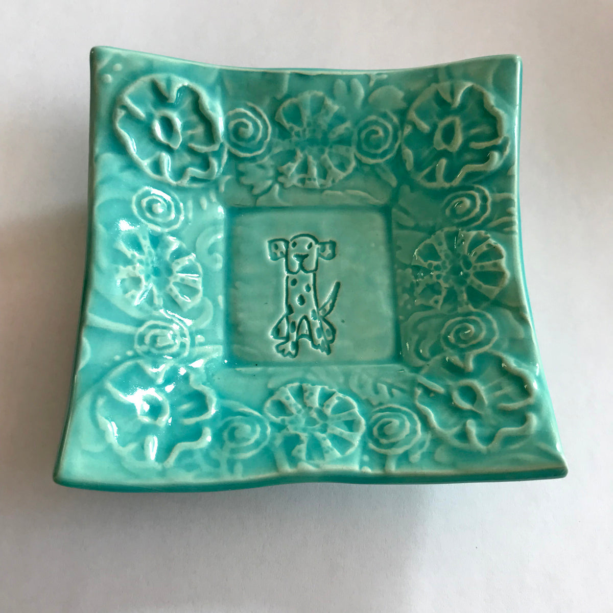 Turquoise glaze enhances dog design on small dish handmade by Lorraine Oerth.