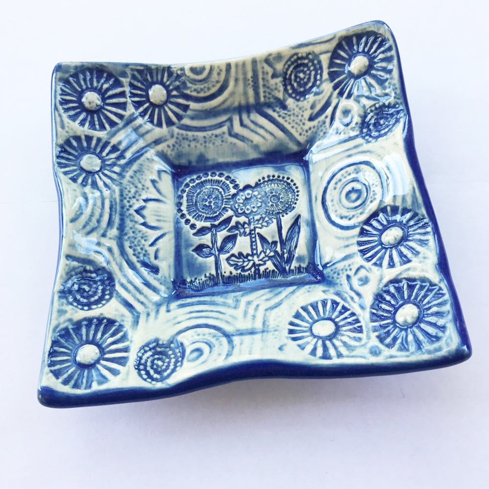 Flower design pottery by Lorraine Oerth with blue glaze.