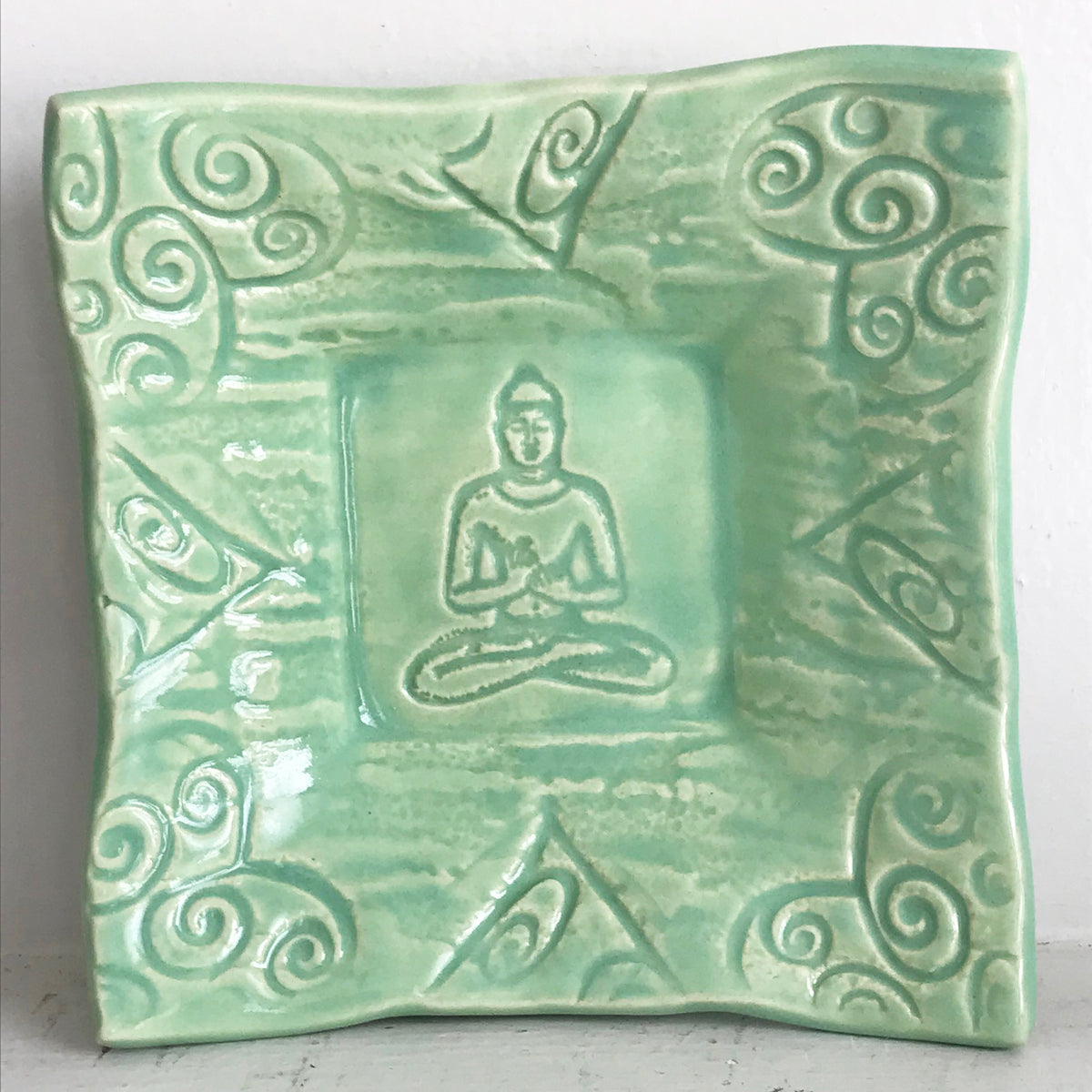Pottery Buddha Dish glazed in celadon green.