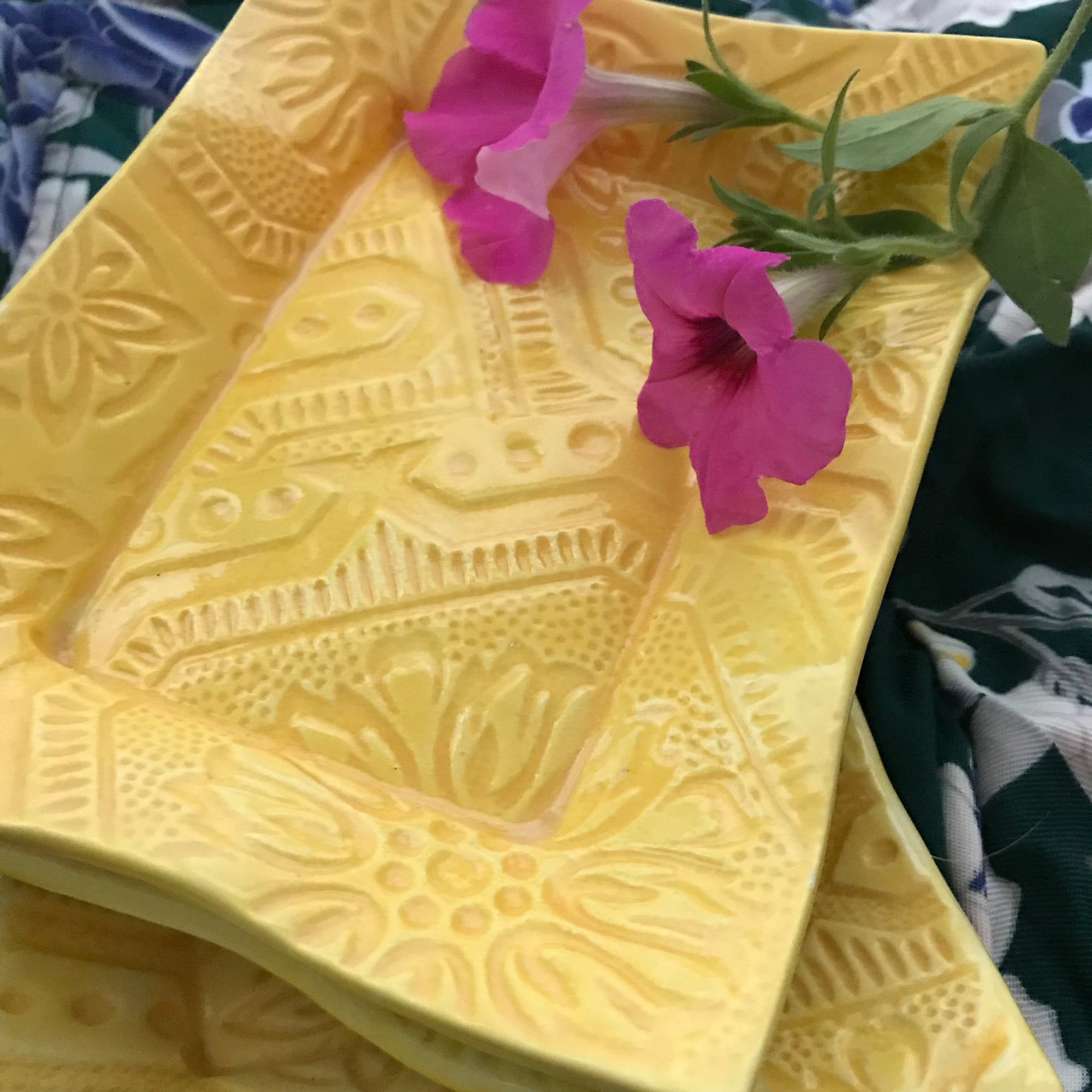 Stunning handmade ceramic tray in yellow glaze shown with magenta flowers. with