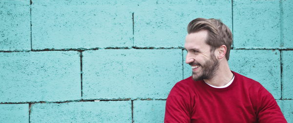 Man with beard in a red sweater by blue brick wall