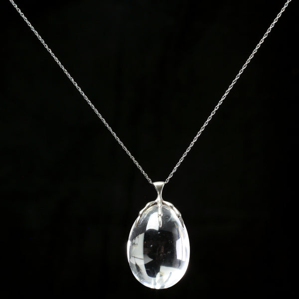 Sterling silver claw clutching clear quartz crystal quail egg pendant hand made by fine jewelry designer Annette Ferdinandsen