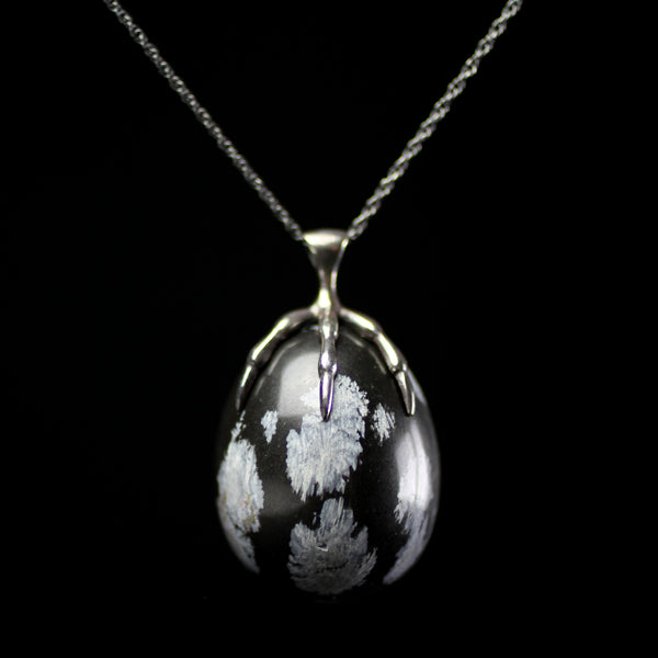Sterling silver claw clutching snowflake obsidian carved stone quail egg pendant hand made by fine jewelry designer Annette Ferdinandsen