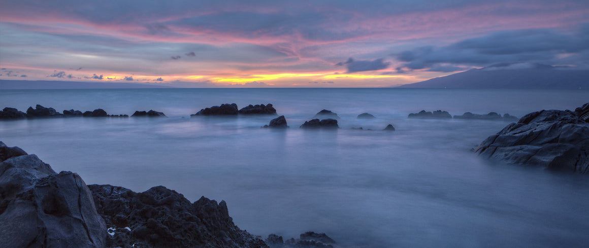 A dark and beautiful sunset shot taken on Maui. The slow shutter speed enables the ocean in the forground to look almost like smoke.