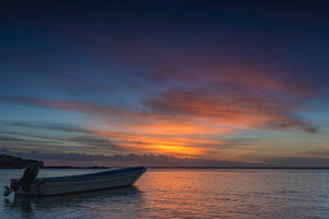 An image of a sunset in Fiji with a local fishing boat sitting alone in the forground.