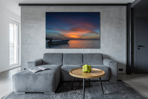 "A modern livingroom scene with a large version of ""Escape"" on the wall above the couch."