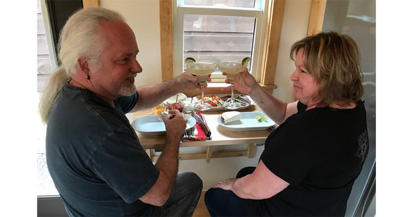 Randy and Yvonne toasting in tiny home