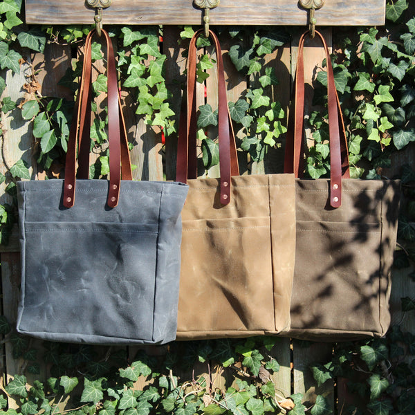 "The Jessamine Market Tote is the perfect everyday tote … not too big, not too small … just right. Two front exterior pockets for easy to reach items and a laptop or tablet pocket inside.  We have made the straps at an 11"" drop, perfect to carry on your shoulder or in your hand, and we have extended them down the back to stash sweaters or scarves. Made in our Louisville, KY studio from #10 Martexin Waxed Duck with veggie tanned bridle leather straps, reinforced with solid copper hand hammered rivets."