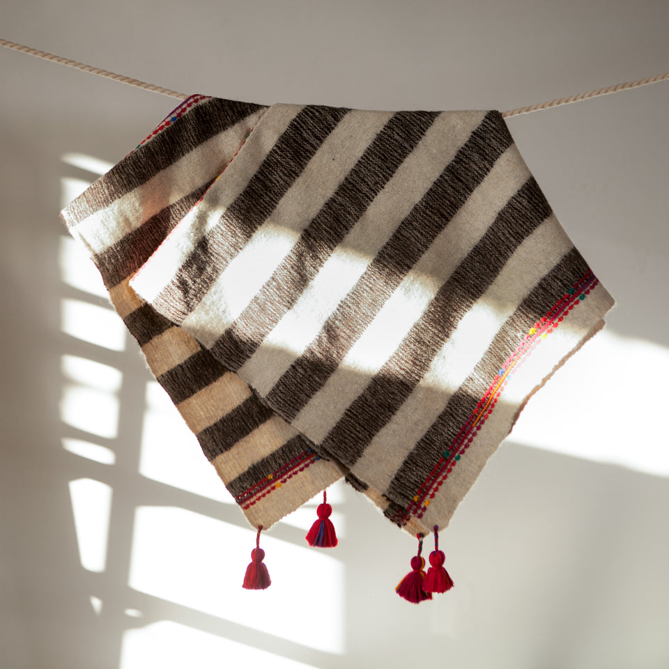 Handwoven wool throw with red tassels black and white stripes
