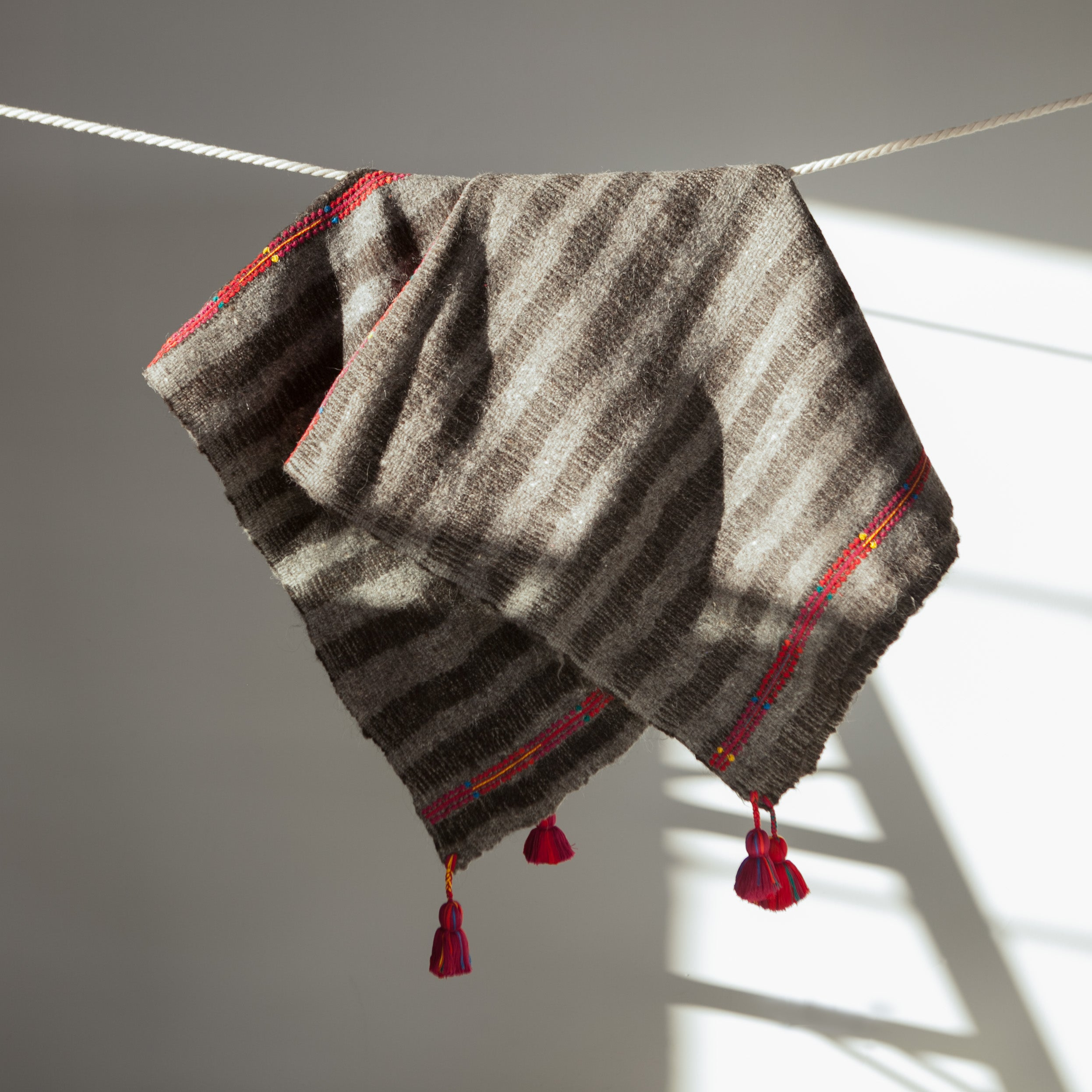Handwoven wool throw with red tassels black and grey stripes
