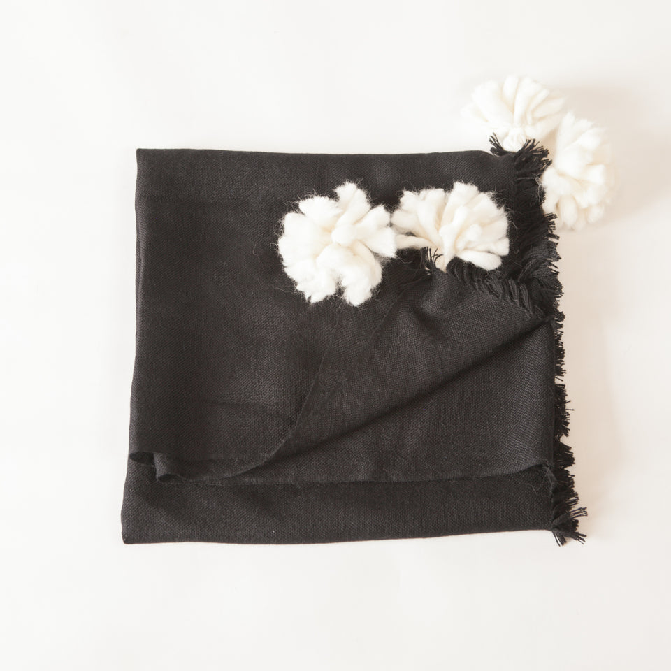 Handwoven merino wool black throw with white poms