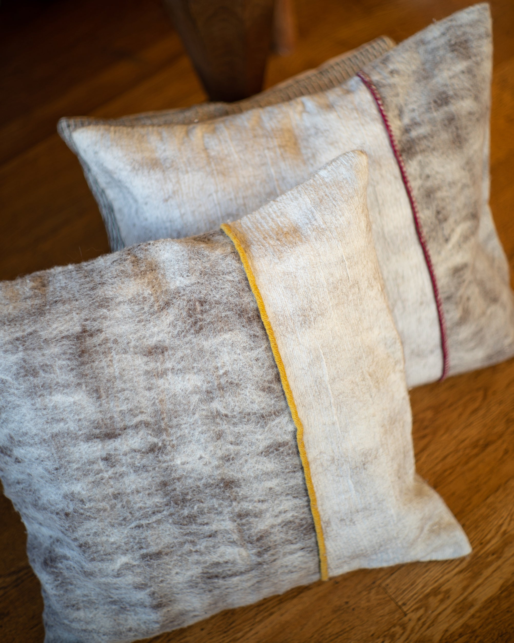Hand-felted silk and wool pillow with red and yellow trim