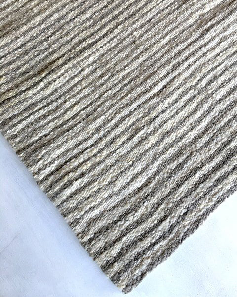 Handwoven wool rug warm grey and white