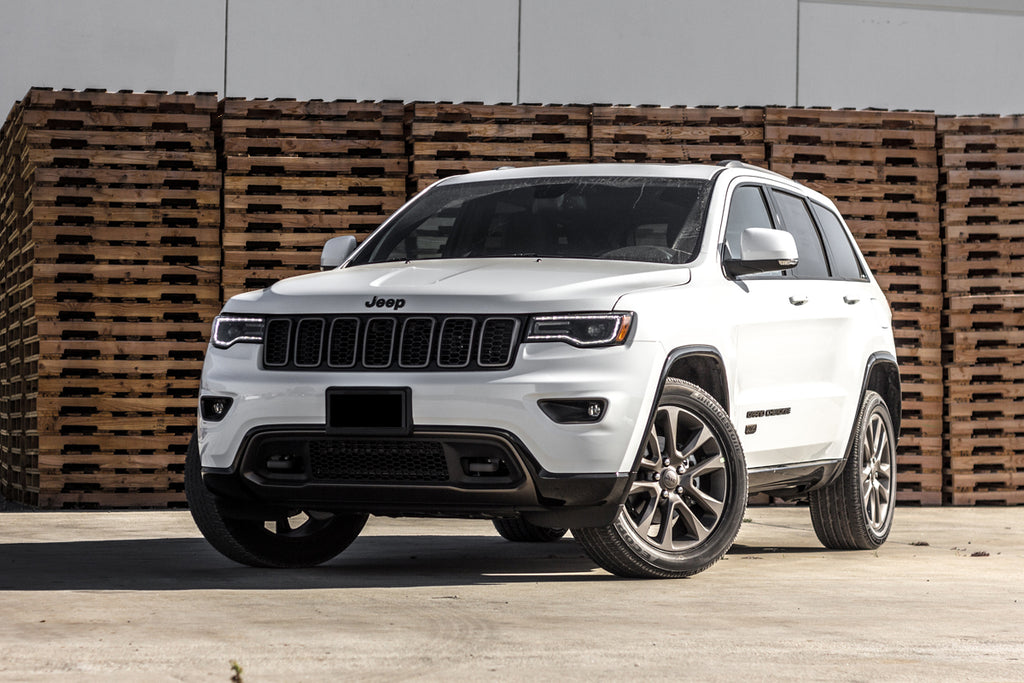 White Grand Cherokee in front of stacked pallets