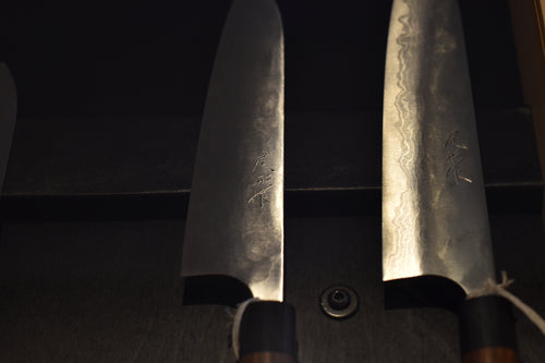 Photo of two knives on display with dramatic lighting