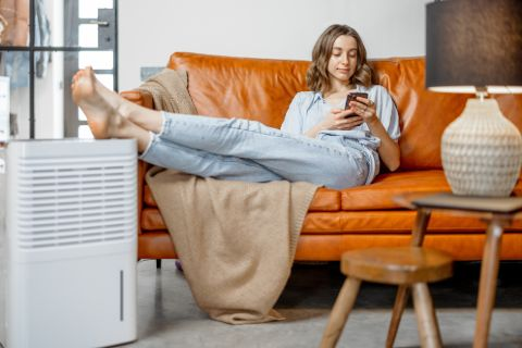 Woman relaxing on an orange couch with her feet resting on an air purifier