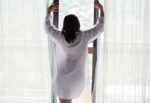 woman opening curtains to reduce essential oil molecules