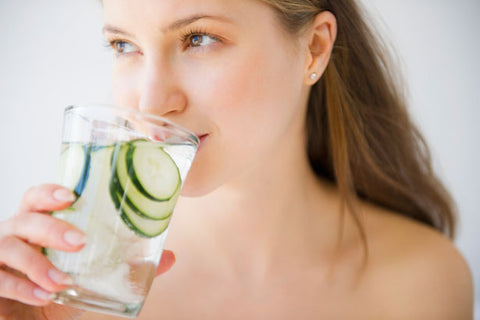 a woman drinking water with cucumbers in it