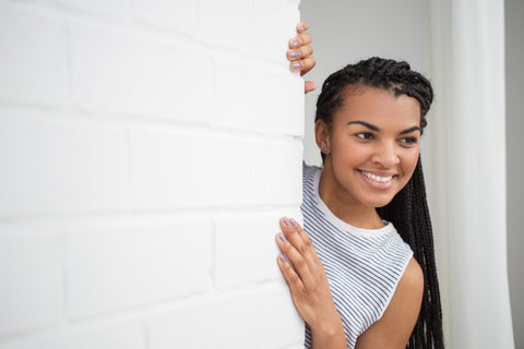 smiling woman peeping from behind wall