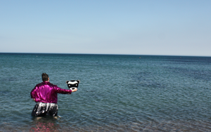 women with pink sequence jacket standing in the middle of the sea holding up a ferret sign