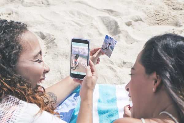 Women on beach viewing Lifeprint photo - Lifeprint photo printer for iPhone and Android