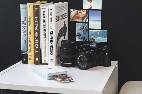Lifeprint printer printing photo, with books and camera behind