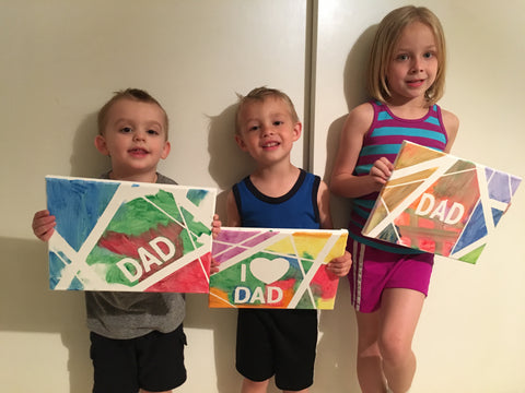 Children holding Father's Day canvas crafts