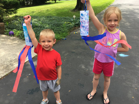 Kids holding finished windsock paper craft