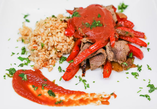 Beef Carne Asada with Fajita Style Peppers & Onions, Seasoned Red Brown Rice, and Smothered with House Made Mild Red Enchilada Sauce