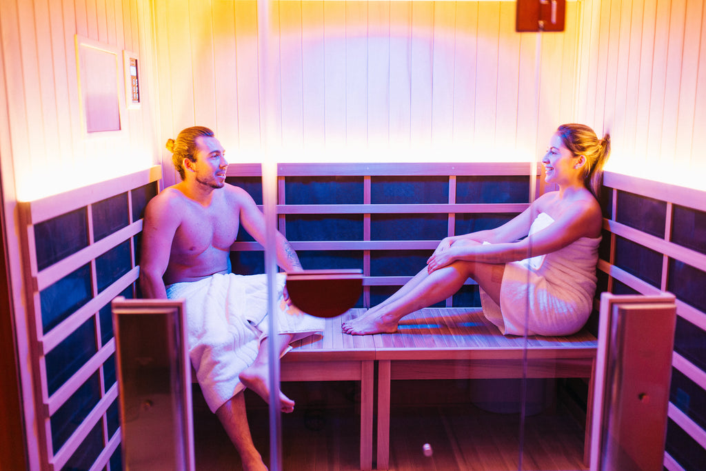 A couple conversing in an infrared sauna featured at Radiance Float + Wellness.
