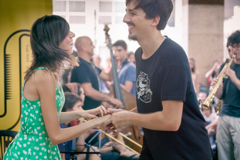 a man and woman dancing together while a jazz band plays