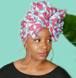 Woman with a pink and blue head wrap on with a bow in the front