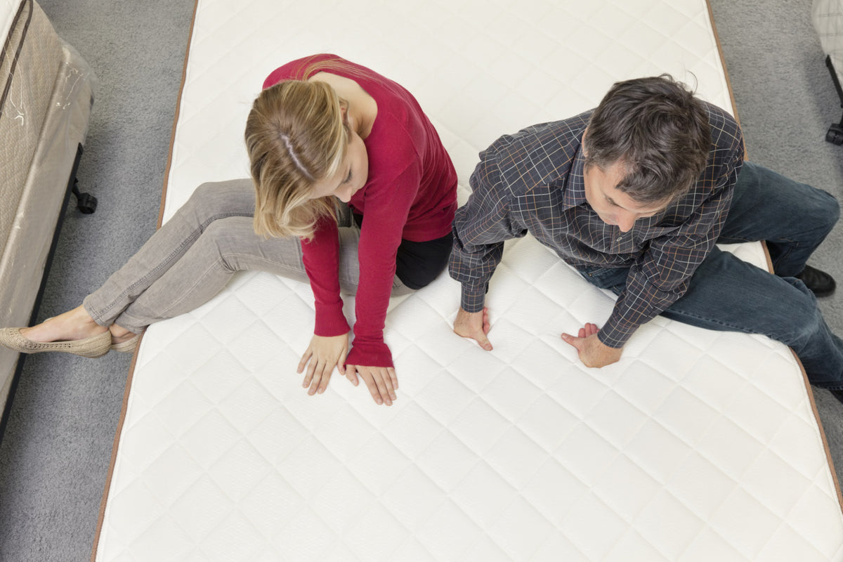 Woman and man evaluating bed quality