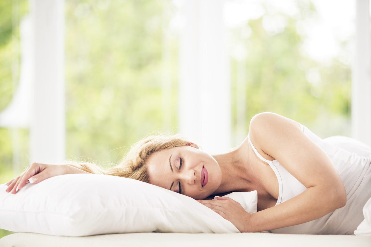 Woman wearing white sleeping comfortably in a cool bed