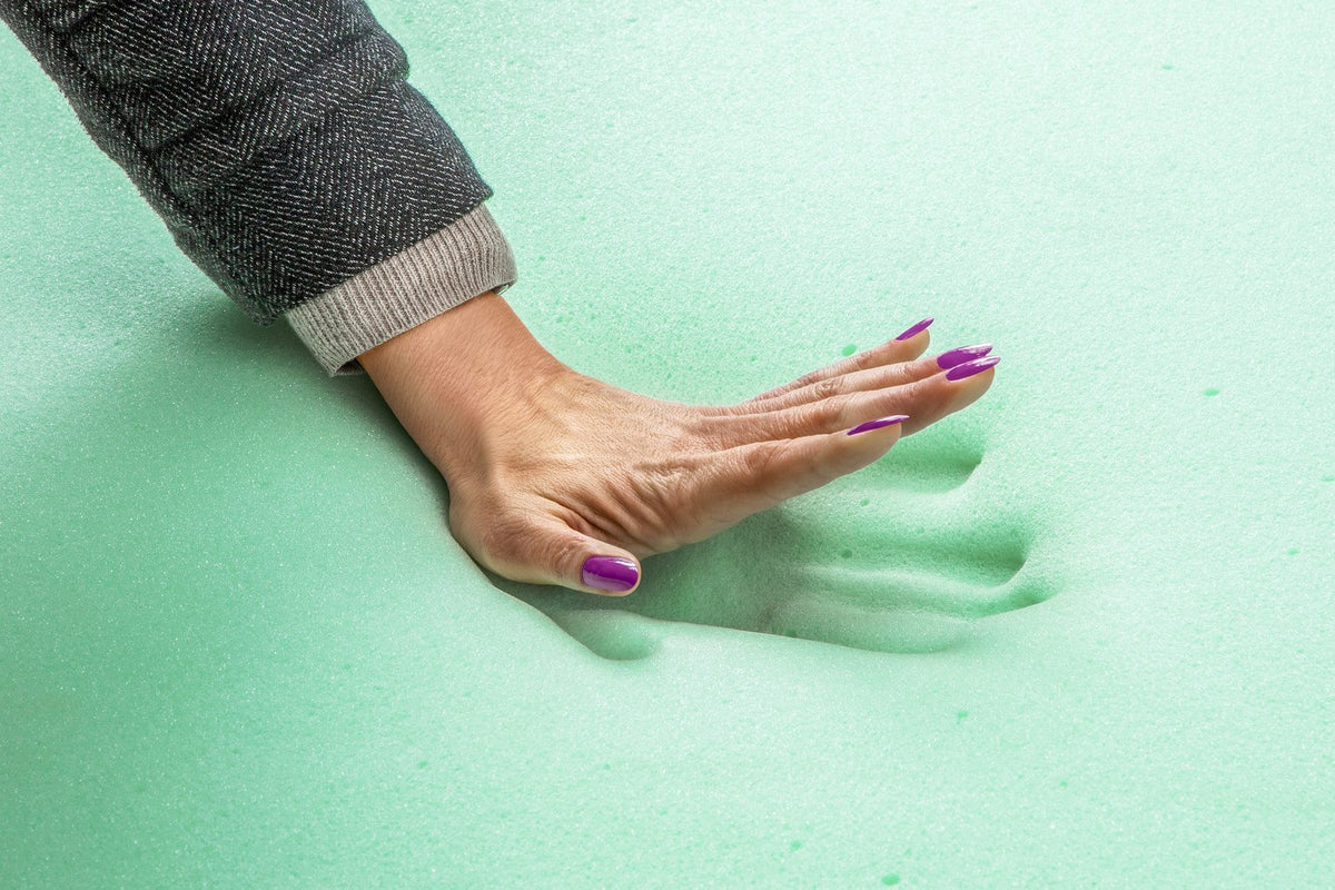 A hand pushing into a memory foam mattress