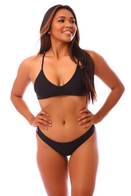 Young woman in low-cut black swim bottoms.