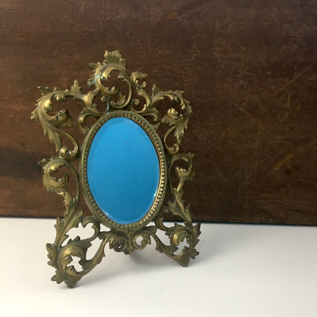 Ornate brass finish vanity mirror - oval beveled glass - 1960s - NextStage Vintage