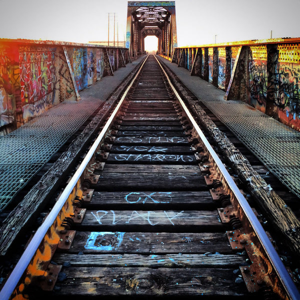 A photo looking down a long set of train tracks in Los Angeles, California with graffit. Photo is a free high resolution stock image to use any way you choose.