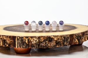 Gemstone roller bottle insert set with lapis lazuli, carnelian, clear quartz, rose quartz, hematite, amethyst and yellow tiger's eye on wood slab