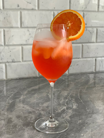 Picture of a glass of aperol spritz on a carrera marble counter