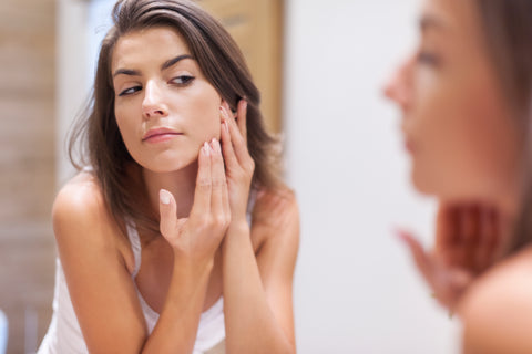 Woman examining her skin in the mirror