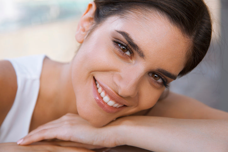 Young woman with clear, olive-toned complexion, smiling