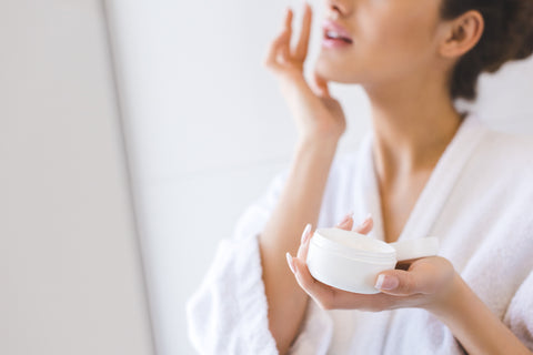 Woman applying face cream while wearing a white terry cloth bathrobe