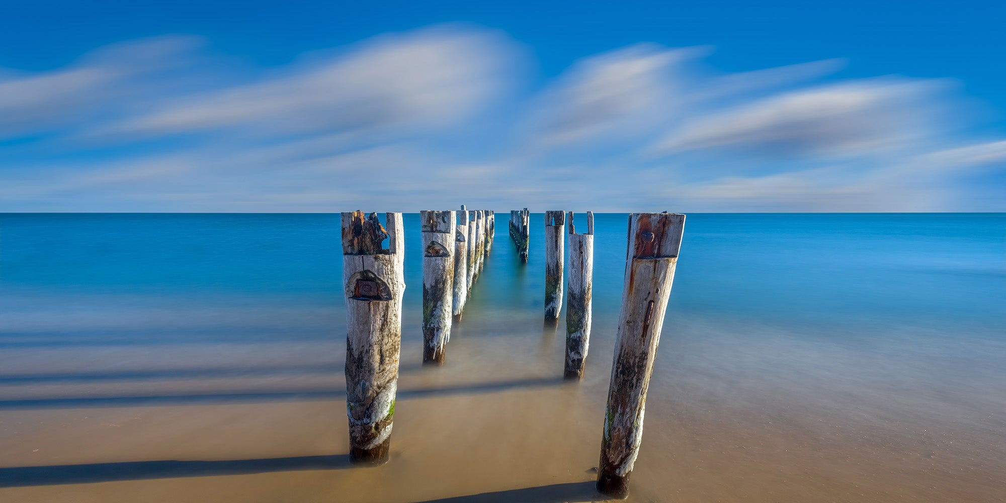 Landscape photograph of decaying pilings on a beach in Falmouth, Massachusetts - by Jonathan Elcock