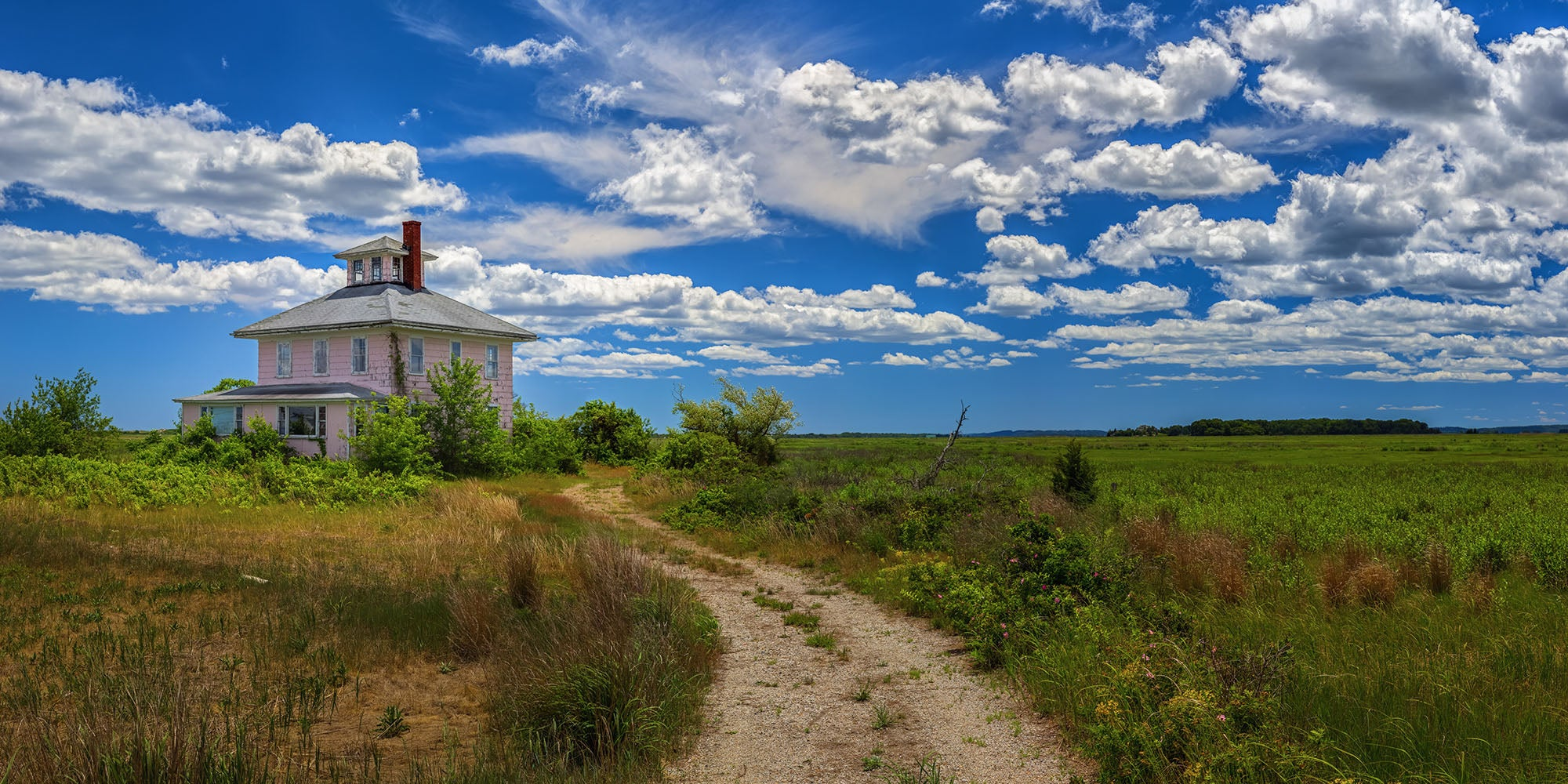 Landscape wall art photography of the iconic Plum Island pink house on a sunny blue sky day